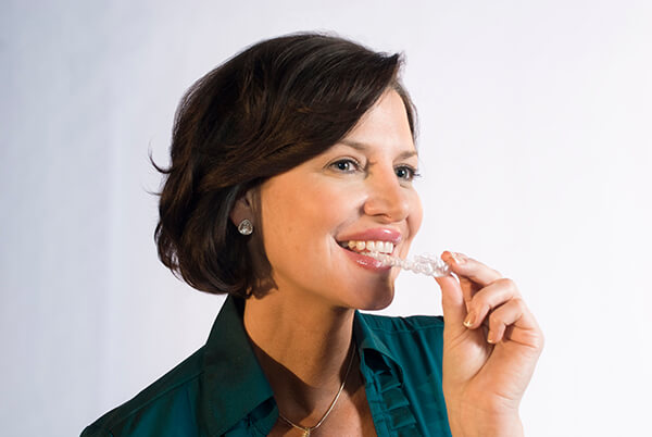 Photograph of a woman putting an Invisalign aligner in her mouth