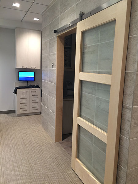 A sliding door to a room next to a computer monitor